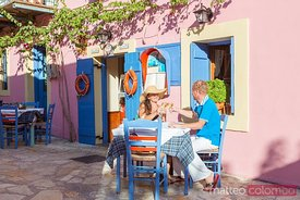 Couple drinking out in a greek village in summer. Kefalonia, Greek Islands, Greece