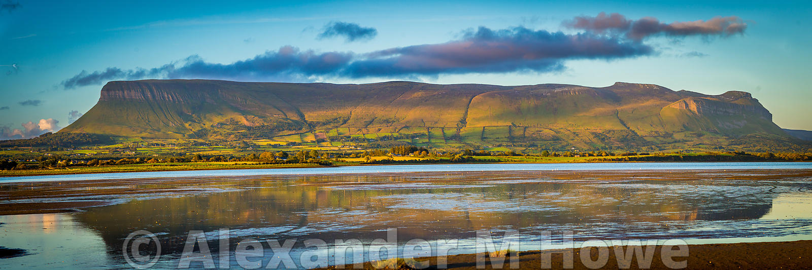 The imposing Benbulbin rock bathed in evening sunlight reflecting in the water of Donegal Bay