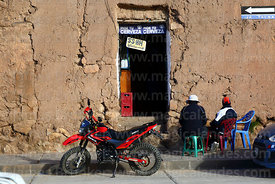 Men sitting outside beer shop on Plaza de Armas, Juli, Puno Region, Peru