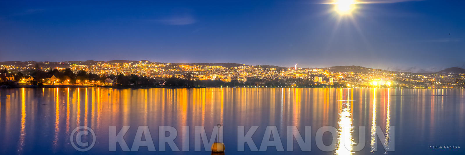 Lausanne by night under the full moon with refelection on Lac Léman