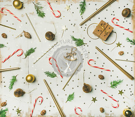 Flat-lay pattern of holiday decoration objects, toys, candles, candy canes, tree branches, box on white background