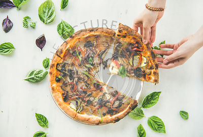 Woman's hands taking Freshly baked vegetarian pizza over marble background
