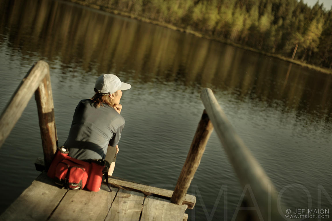 Woman sitting on board pontoon by lake