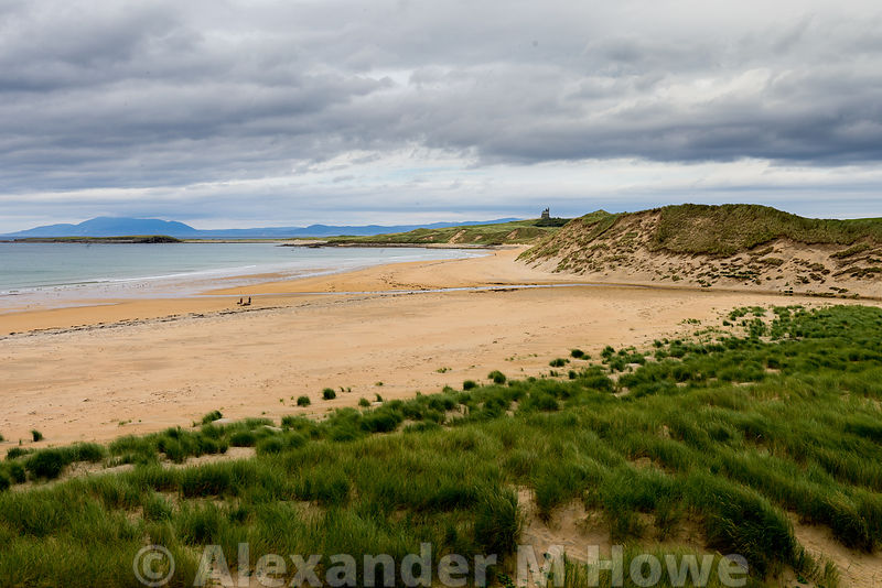 Cliffony beach of yellow sand with green vegetation and dark brooding skies