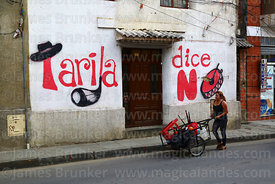 "Woman pushing cart walking past ""Tarija Says No"" political mural on house, Tarija, Bolivia"