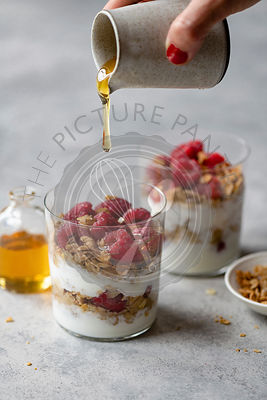 Honey Pouring over Raspberry Parfait