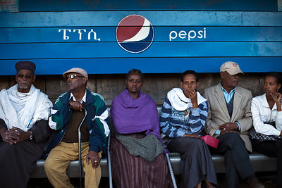 Ethiopia - Addis Ababa - People wait for a bus underneath and hand-painted sign advertising Pepsi