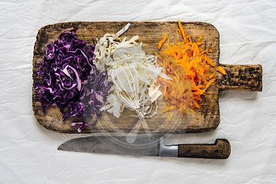Shredded white cabbage, purple cabbage and carrot ready on a wooden board for coleslaw photographed from top view.