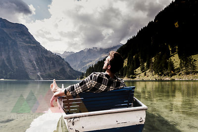 Austria, Tyrol, Alps, relaxed man in boat on mountain lake