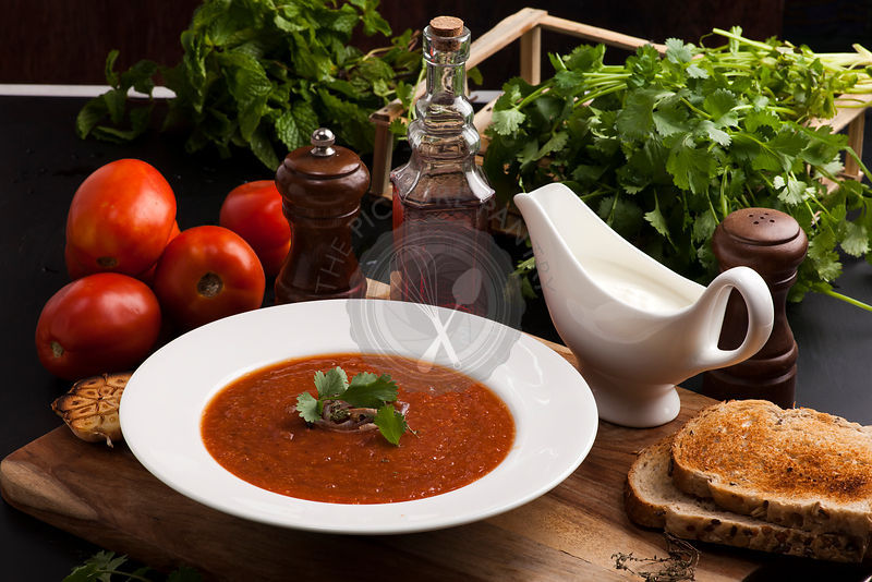 Bowl of roasted delicious tomato soup, garnished with herbs and roasted onion, served with creme