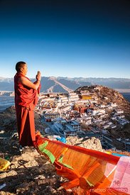 Buddhist monk praying in front of Ganden monastery, Tibet
