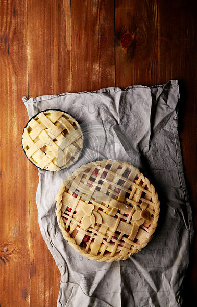 Apple, strawberry and raspberry pies uncooked on red wooden background