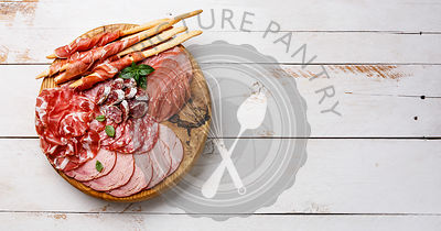 Cold meat plate Italian snacks food with ham, prosciutto, salami, pork chops, sausage and grissini bread sticks on wooden background copy space