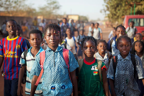Fille rentrant de l'école à 17h avec ses collègues de classe à Ouagadougou, Burkina Faso / Girl returning from the school at 5 pm with his class colleagues in Ouagadougou, Burkina Faso
