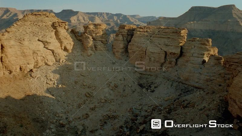 Aerial close up, up side of mountain to rocky formations on top, through gap to river below Fish River Canyon Namibia