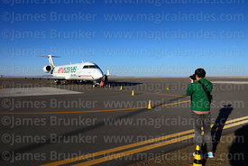 Asian tourist taking photo of Amaszonas Canadair CL 600 2B19 Regional Jet CRJ 200LR at Uyuni airport, Bolivia