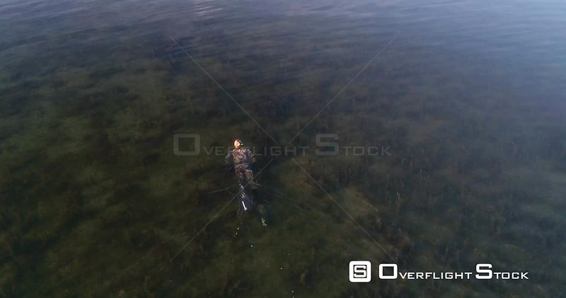 Diver on the sea, aerial  rising view of a spearfisher, at the clear, shallow and low waters of baltic sea, on a sunny summer evening sunset, in Hanko, Finland