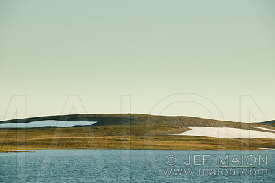 Tundra and lake below empty sky