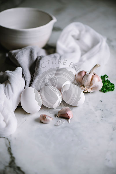 White eggs with garlic cloves on a marble worktop in a kitchen
