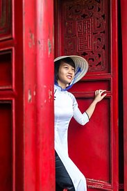 Young vietnamese girl in local dress near red carved door
