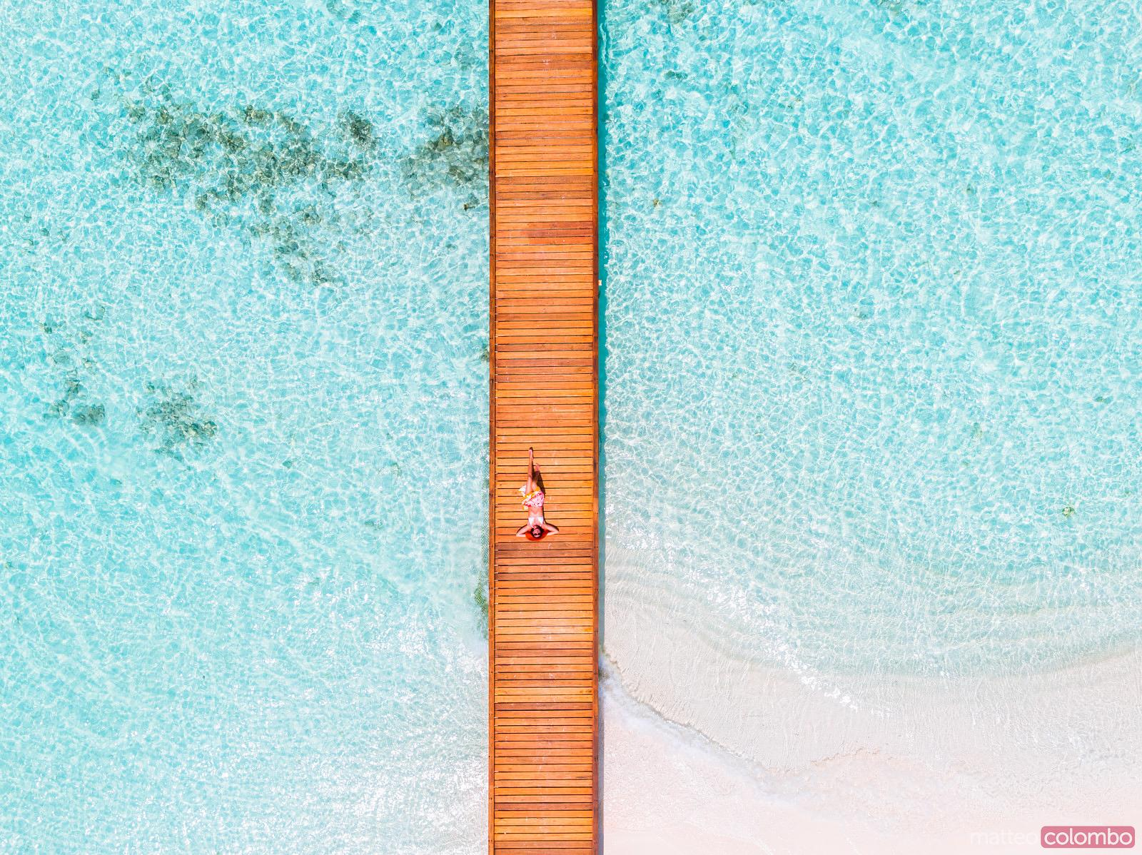 Overhead view of woman lying down on jetty, Maldives