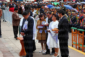 Hosting family (alferado) waiting to present gifts before holy communion during central mass for the Virgen de la Candelaria festival, Puno, Peru