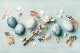 Painted eggs for Easter, feathers and blooming almond flowers