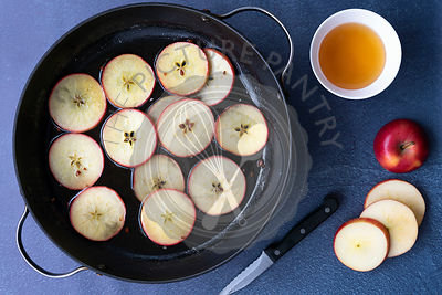 Sliced apples in a pan of honey syrup with a bowl of honey, a knife and a sliced apple.