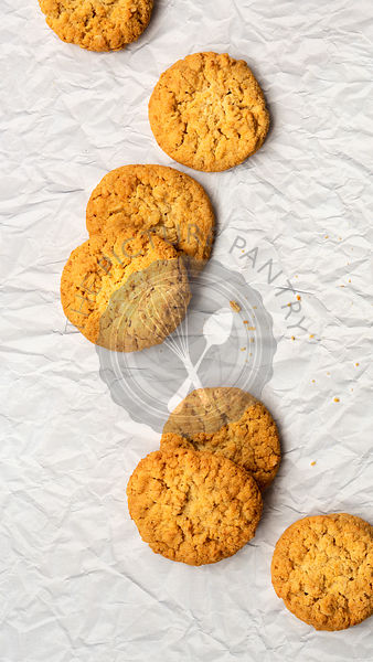 Golden homemade honey and oatmeal biscuits on a textured paper backgound.