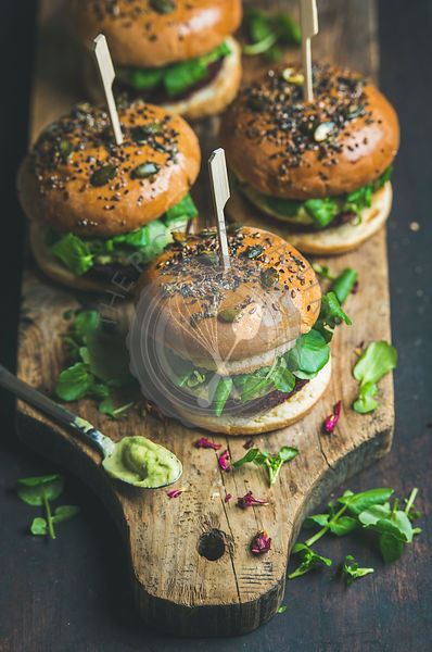 Healthy vegan burger with beetroot and quinoa patty, arugula, avocado sauce and wholegrain buns on rustic wooden board over dark wooden background