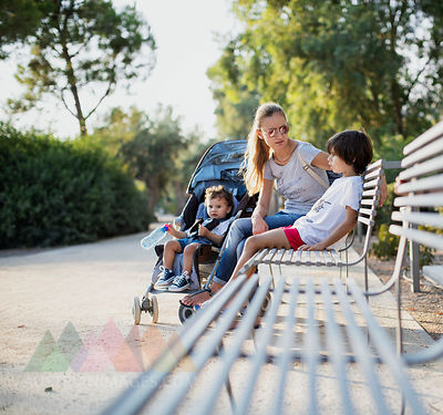 Mother sitting on park bench, talking to one of her sons