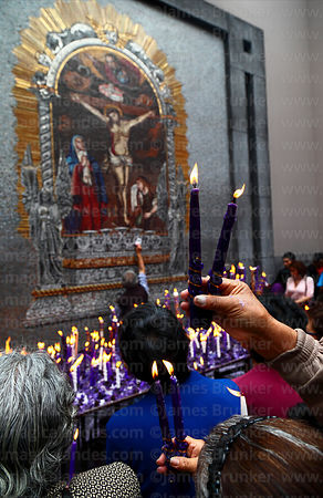 Devotee offering candles to Señor de los Milagros mosaic in courtyard behind Las Nazarenas church, Lima, Peru