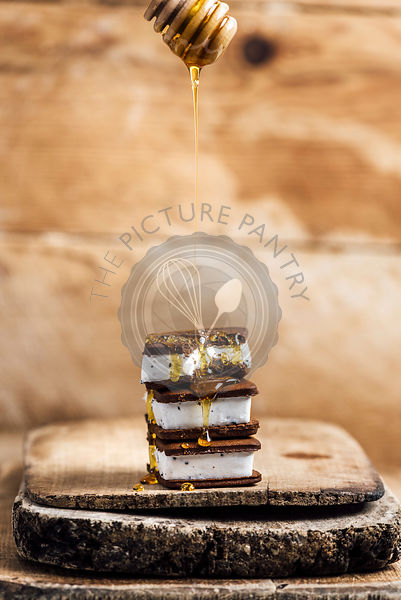 Ice Cream Sandwiches are piled on one another and drizzled with honey on a wooden board.