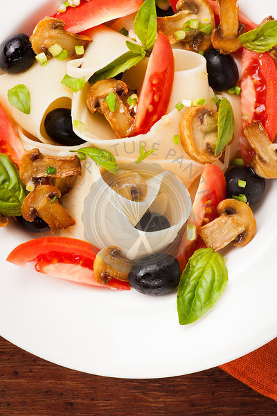 Pasta pappardelle with mushrooms, tomatoes, olives and basil leaves