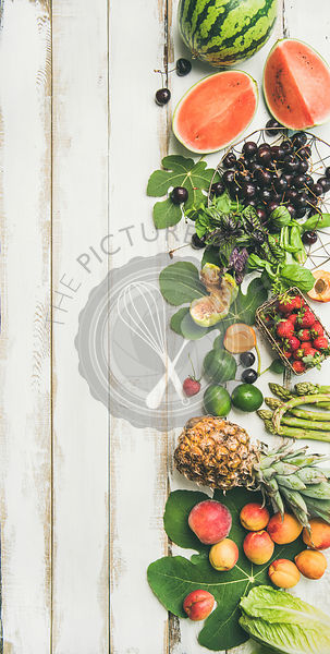 Seasonal fruit, vegetables and greens over wooden background, vertical composition