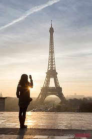 Woman taking a snapshot of the Eiffel tower, Paris, France