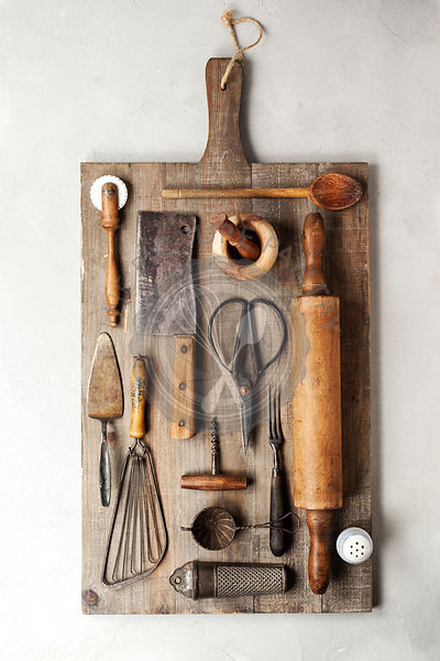 Top view of a group of vintage cooking utensils on a wood cutting board.