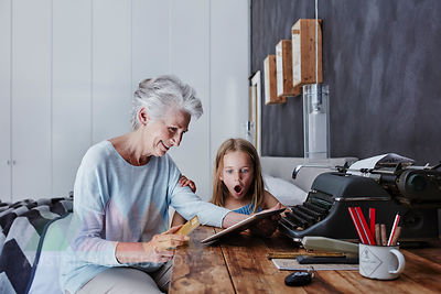 Grandmother and amazed granddaughter shopping online at home