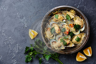 Mussels Clams Kiwi with parmesan cheese in cooking pan on black background