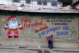Mother and child walking past Father Christmas mural on wall of the offices of an electricians and electrical workers cooperative, La Paz, Bolivia