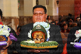A man holds a skull called Jordan  wearing a police cap during mass in church, Ñatitas festival, La Paz, Bolivia