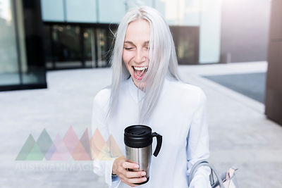 Screaming young businesswoman holding coffee mug in the city