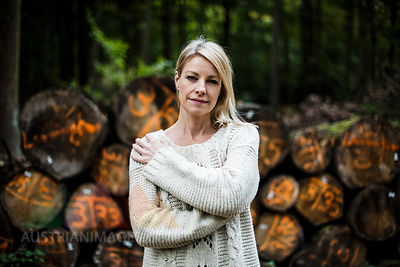 Portrait of blond woman at stack of logs in the forest
