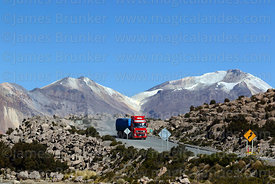 Truck on Highway 11, volcanos on Chile / Bolivia border in background, Lauca National Park, Region XV, Chile