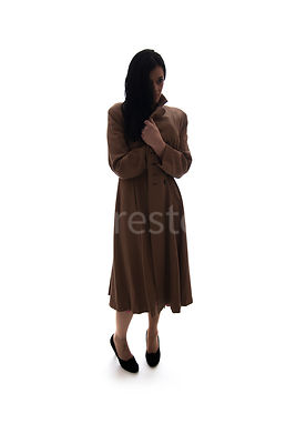 A silhouette of a 1940's mystery woman in a coat – shot from eye-level.