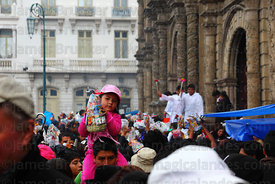 Priests blessing crowds of people and their miniatures with holy water outside San Francisco church, Alasitas festival, La Paz, Bolivia