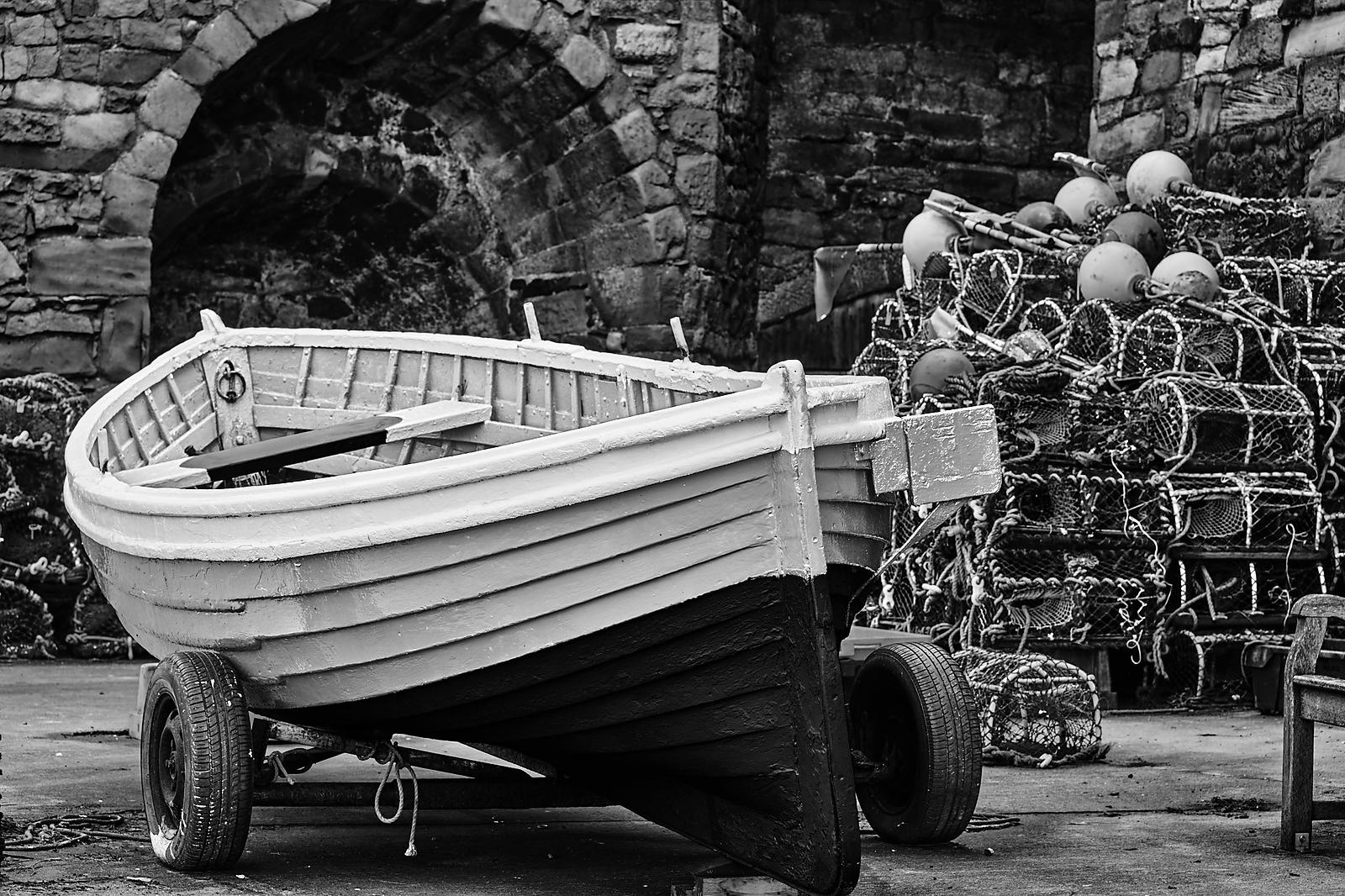Fishing boat and lobster pots against a stone wall in black and white