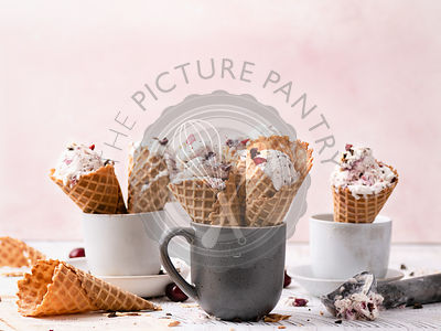No churn vanilla ice cream with dark chocolate and cherry chunks in waffle cones.