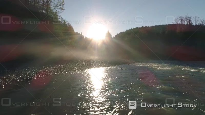 Drone flying sideways in misty wilderness with river flowing through Pacific Northwest forest