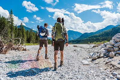 Germany, Bavaria, back view of two hikers walking in dry creek bed